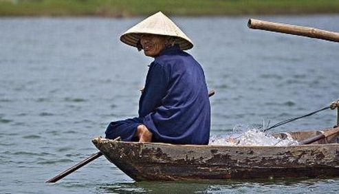 Old man in fishing boat, hoi-an, central vietnam