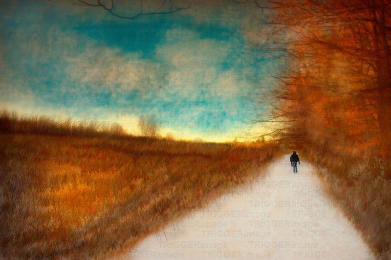 A figure walking alone down a long path